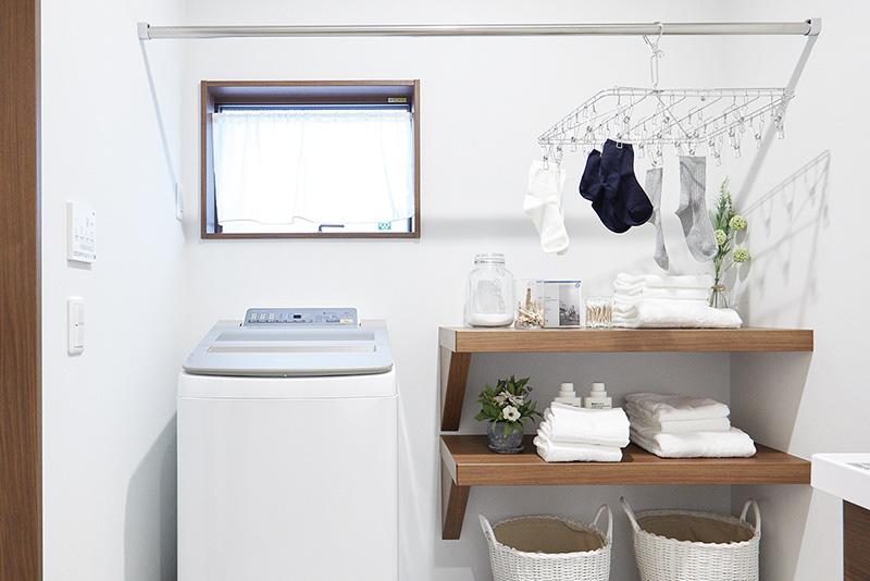 洗濯がここだけで片づく、洗濯機も置ける室内干しスペース。スムーズな動線で、バルコニーへもそのまま出られるので、天気や時間に関係なく干せて、外干しと室内干しを移すのも手軽です。風を通しつつ、外からの視線は遮るよう工夫されています。
